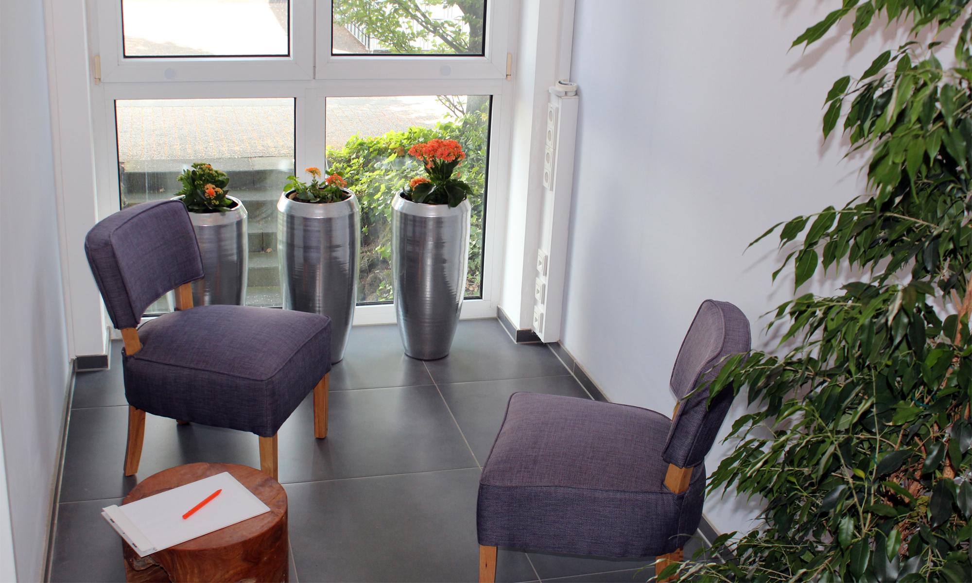 Besprechungsraum zwei Sessel Tisch drei Bodenvasen Block Stift